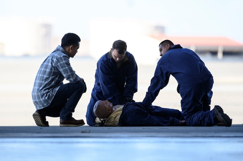 A group of Airmen huddle around a training dummy. The flight line is in the background.