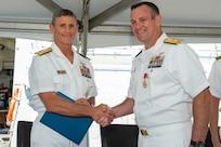 Vice Adm. Andrew Lewis, Commander, U.S. 2nd Fleet, presents Rear Adm. Craig Clapperton, Commander, Carrier Strike Group (CSG) 12,