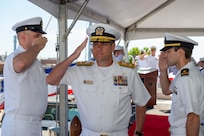 Rear Adm. Craig Clapperton, Commander, Carrier Strike Group (CSG) 12, salutes the side-boys as he is welcomed to the CSG-12 Change of Command