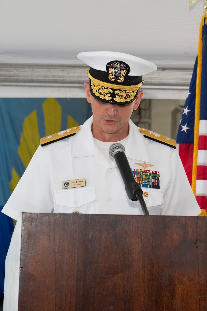 Rear Adm. Gregory Huffman reads his orders during the Carrier Strike Group (CSG) 12 Change of Command ceremony a