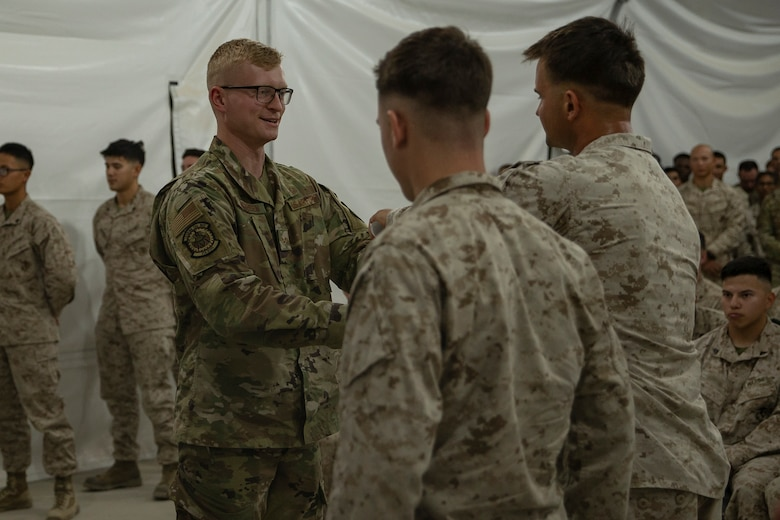 Photo of Airman receiving course certificate.