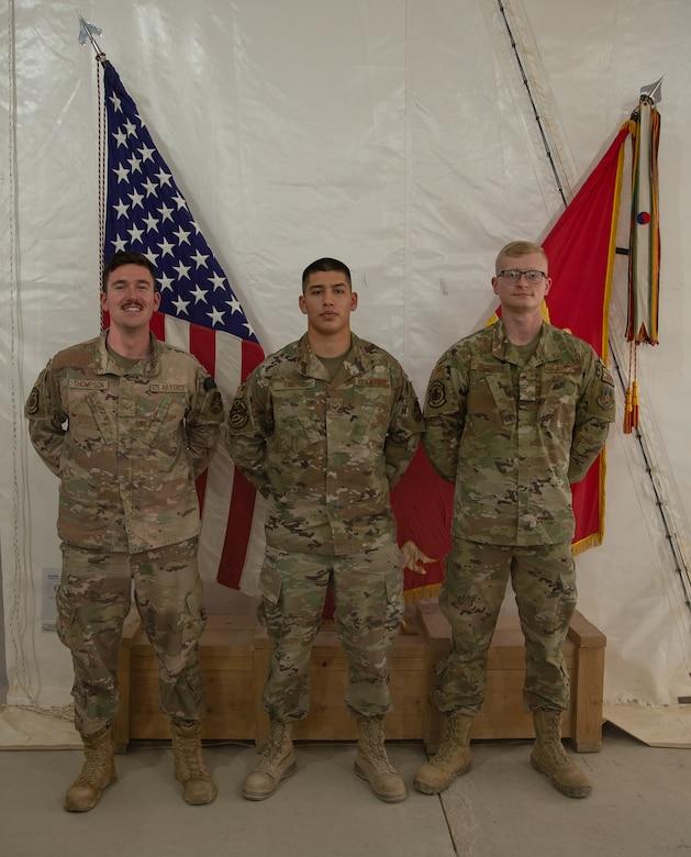 Three graduates pose for a photo.