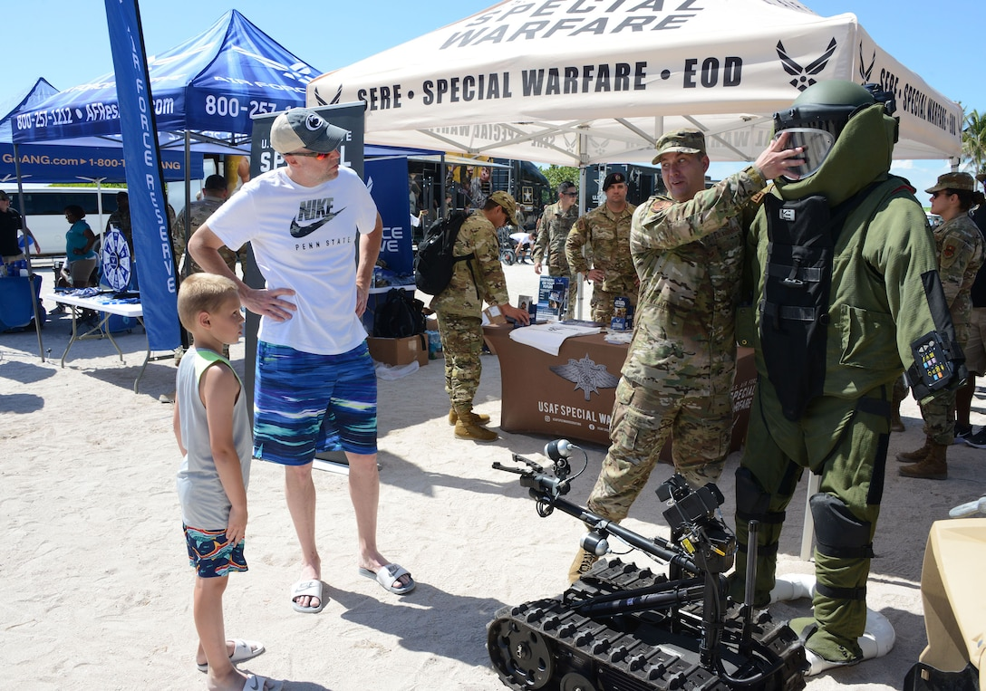 Staff Sgt. Jonathan Stapleton, 330th Recruiting Squadron special warfare recruiter and explosive ordinance technician, explains the EOD bomb suit to a young man and his father at the Miami Beach Air Show, May 28, 2021.