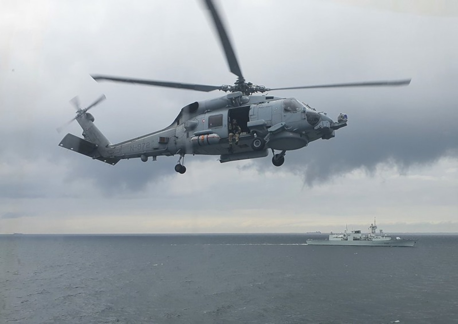 The embarked MH-60 Seahawk Helicopter (RAIDER) of Standing NATO Maritime Group One (SNMG1) ship HDMS Absalon participates in a Naval Gunnery Support (NGS) training serial in the Baltic Sea on June 12, 2021 during Exercise BALTOPS 50. SNMG1 Flagship HMCS Halifax can also be seen in the background of the image. RAIDER acted as a spotter for HDMS Absalon and coordinated the NGS fires with elements located ashore from enhanced Forward Presence (eFP) Poland, enhanced Forward Presence (eFP) Estonia, and the German 9th Panzer Division at the Putlos Training Area Range in Germany. NATO warships are highly skilled and experienced at joint warfighting operations and can be called upon to engage and if necessary, neutralize targets ashore with precise naval gunnery in support of amphibious or land forces operations. BALTOPS is an annual joint, multinational maritime-focused defence exercise designed to enhance interoperability, flexibility, and demonstrate resolve among Allied and partner forces to defend the Baltic Sea Region. It involves maritime and air forces, strengthening combined response capabilities necessary to ensure regional security and stability.