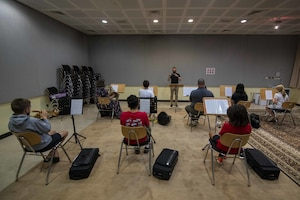 U.S. Air Force 1st Lt. Brandon Hults, AFCENT Band officer in charge, conducts students from the Junior Symphonic Winds at the Qatar Music Academy, June 15, 2021, Doha, Qatar.  Members of the AFCENT Band worked with students during class and played alongside them during rehearsal. The AFCENT Band uses community engagement opportunities like school visits to share the Air Force mission through music. (U.S. Air Force photo by Tech. Sgt. Dylan Nuckolls)