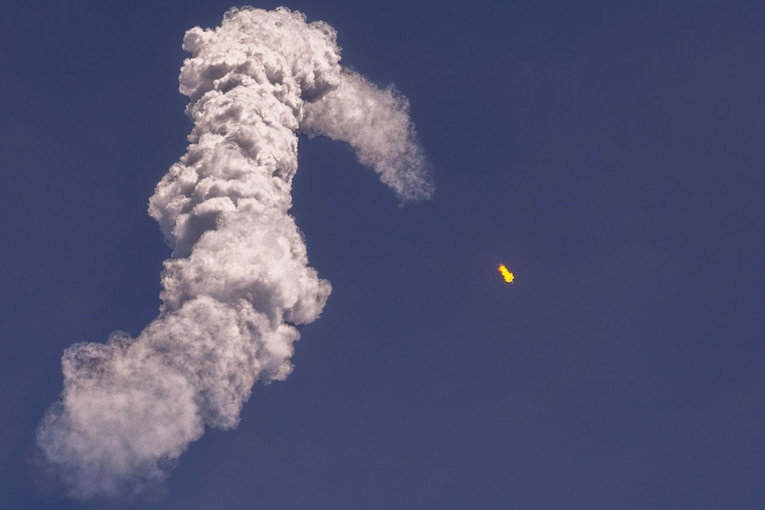 A satellite launches leaving an arc of thick smoke.