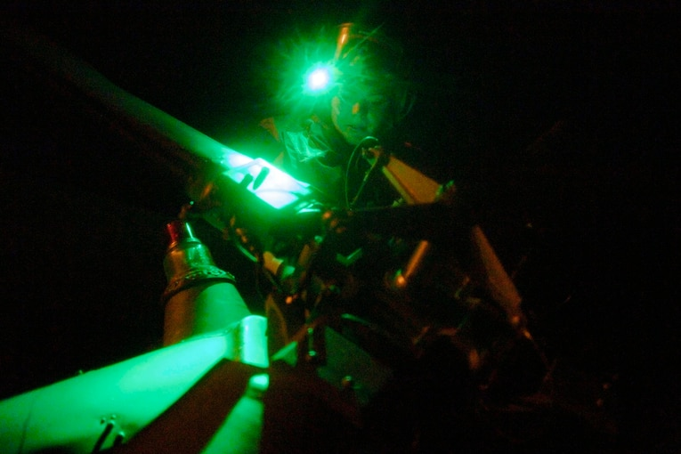 A sailor illuminated by green light works on an aircraft rotor at night.