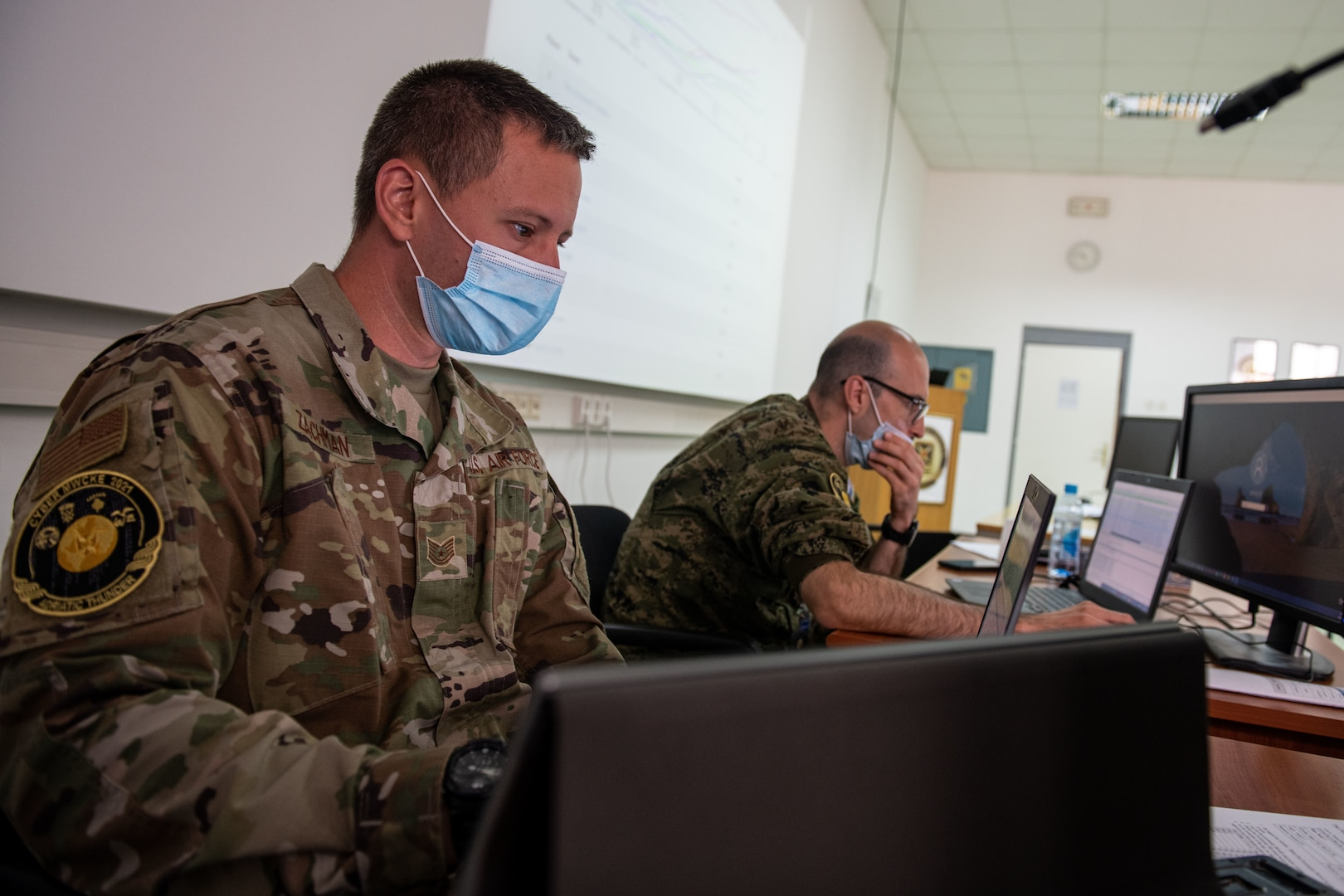 U.S. Air Force Tech Sgt. Jared Zachman, a cyber analyst with Minnesota National Guard Joint Force Headquarters Defensive Cyber Operations Element, works alongside Croatian Armed Forces service member 2nd Lt. Domagoj Volarevic during cyber training prior to the start of the joint cyber training exercise, Midwest Croatia Kosovo Exercise Adriatic Thunder at Dr. Franjo Tudman Croatian Military Academy, Zagreb, Croatia, on June 14, 2021.