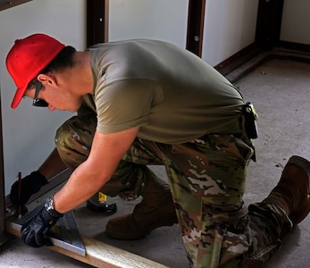 An Airman from the 201st Red Horse Detachment 1, measures out placements for the installation of fixed latrines at Joint Base McGuire-Dix-Lakehurst, N.J., June 12, 2021.The installation related construction brought Soldiers and Airmen from as far a New York to complete their Reserve Annual Training. (U.S. Air Force photo by Staff Sgt. Sabatino DiMascio)