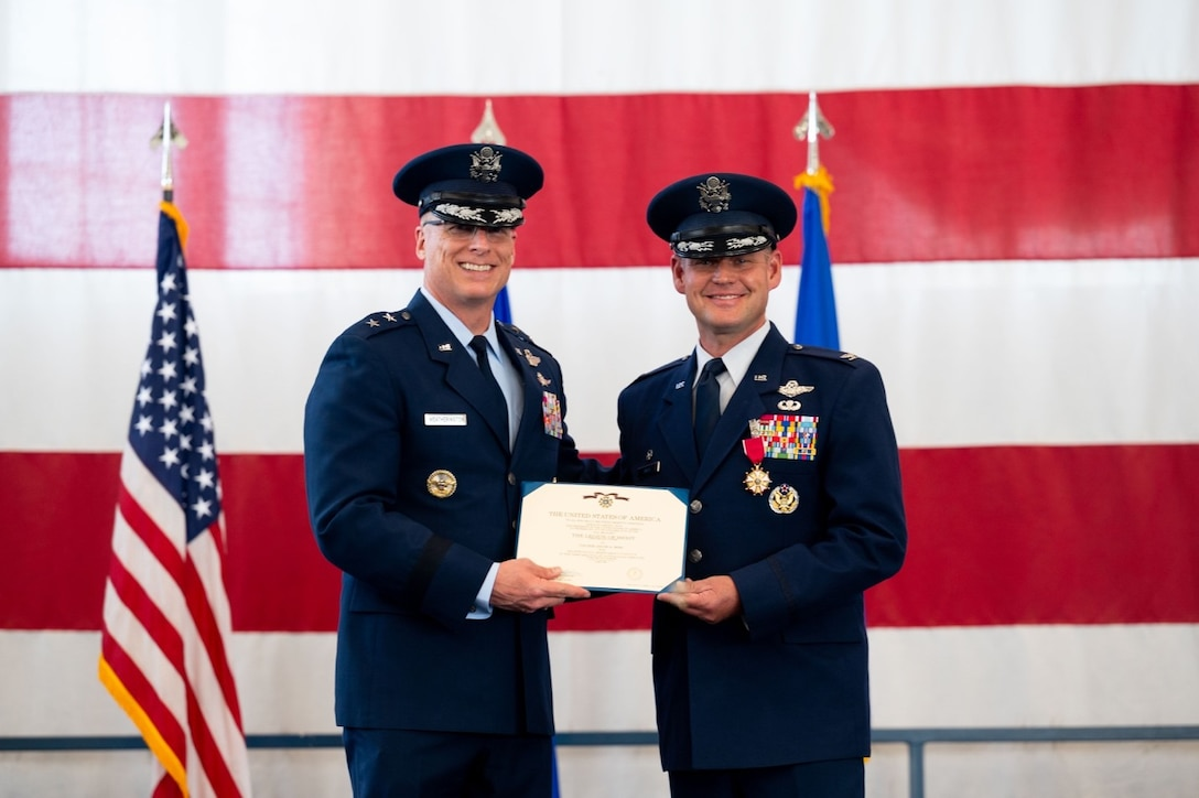 Maj. Gen. Mark E. Weatherington, 8th Air Force and Joint-Global Strike Operations Center commander, presents Col. David A. Doss, the outgoing 28th Bomb Wing commander, with the Legion of Merit during the 28th BW change of command ceremony at Ellsworth Air Force Base, S.D., June 18, 2021.