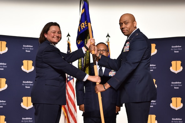 U.S. Air Force Col. Angelina Maguinness, 17th Training Group commander, passes the guidon to Lt. Col. Erwin Mason, incoming 316th Training Squadron commander, during the change of command ceremony at the Base Theater on Goodfellow Air Force Base, Texas, June 18, 2021. Mason was previously the chief for the Middle East and Africa Division at the U.S. Cyber Command in Maryland. (U.S. Air Force photo by 2nd Lt. Steve Garrett)