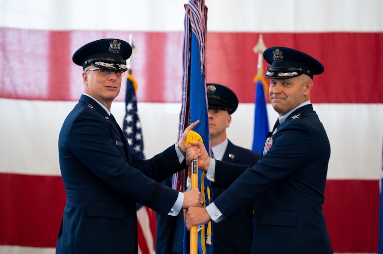 Maj. Gen. Mark E. Weatherington, 8th Air Force and Joint-Global Strike Operations Center commander, presents the guidon of the 28th Bomb Wing to Col. Joseph L. Sheffield, the new 28th BW commander, during a change of command ceremony at Ellsworth Air Force Base, S.D., June 18, 2021.