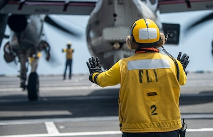Aviation Boatswain's Mate (Handling) Airman Austin Colby, from Spokane, Washington, directs aircraft traffic on the flight deck of the Nimitz-class aircraft carrier USS Harry S. Truman (CVN 75) during Tailored Ship's Training Availability (TSTA) and Final Evaluation Problem (FEP).