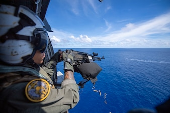 Petty Officer 2nd Class Bryce Hailey fires a M240 machine gun during a live-fire exercise in the Philippine Sea.