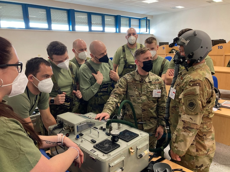 An Airman teaches Czechian Airmen about joint combined aircrew system tester systems.