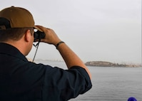 """(JUNE 21, 2021) Cryptologic Technician (Collection) 1st Class Paul Clayton observes Gorée Island through binoculars in preparation for pulling in to Dakar, Senegal aboard the Expeditionary Sea Base USS Hershel """"Woody"""" Williams (ESB 4) in the Atlantic Ocean, June 21, 2021. Hershel """"Woody"""" Williams is on a scheduled deployment in the U.S. Sixth Fleet area of operations in support of U.S. national interests and security in Europe and Africa."""
