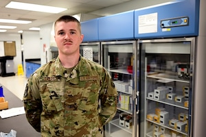An Airman poses for a photo in front of a medical freezer.