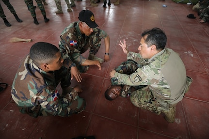 A U.S. Army Soldier with the 2-54th Security Force Assistance Brigade (SFAB) instructs members of the Dominican Republic Special Forces on emergency medical procedures during Tradewinds 2021.