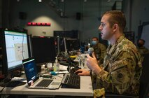An Airman holds a microphone while looking at a computer.