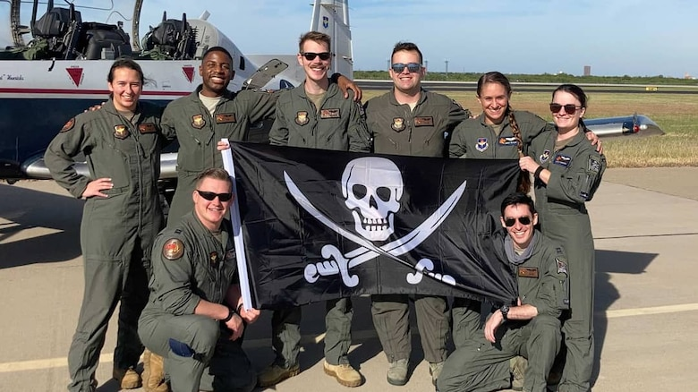 """Eight pilots pose holding black """"FAIP"""" flag with skull and swords"""