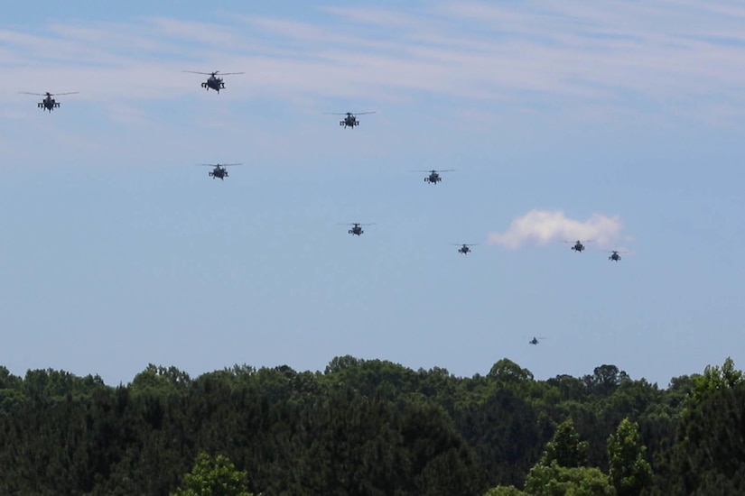 A group of military aircraft fly in formation.