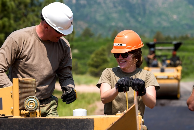 A U.S. Air Force Academy cadet and an enlisted mentor operate a paver on a road in Jack's Valley
