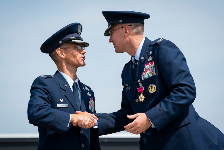 Col. Christopher Leonard, commander of the 10th Air Base Wing (left), shakes hands with his predecessor, Col. Brian Hartless after the wing's change of command ceremony, June 18, 2021.