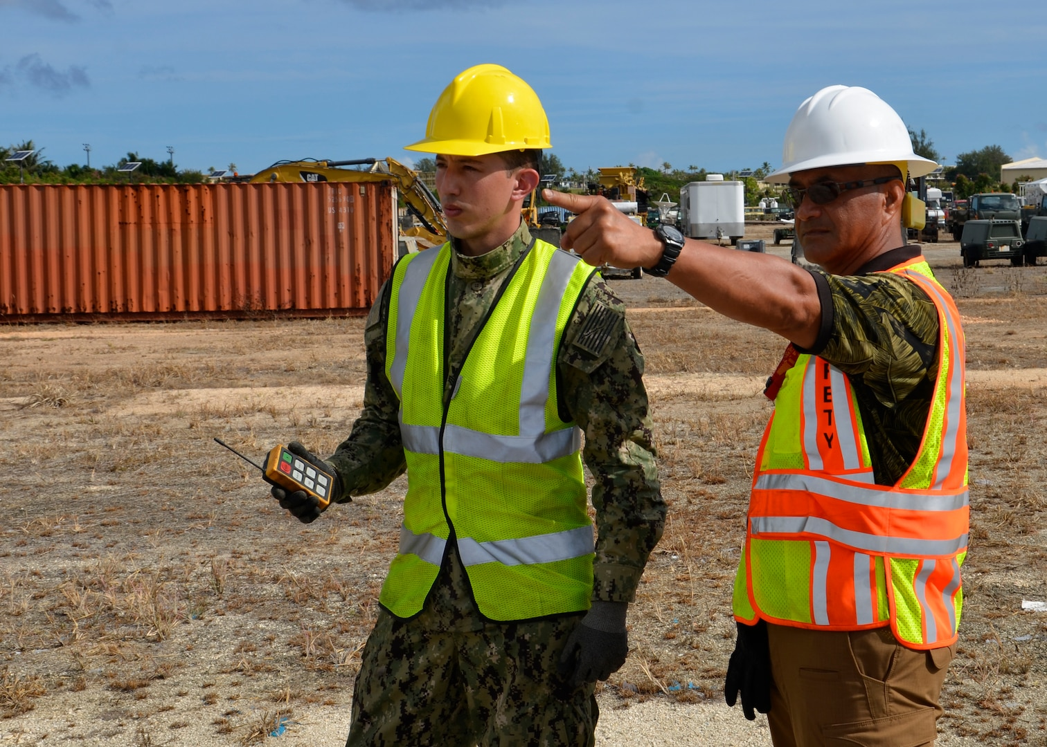 man points in distance while talking to another man, both in safety vest