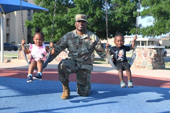 airman poses with two children