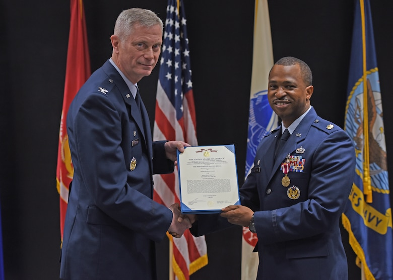 U.S. Air Force Col. Tony England, 17th Mission Support Group commander, presents Maj. Michael Quinn, 17th Contracting Squadron outgoing commander, the Meritorious Service Medal during the 17th CONS change of command ceremony at the Event Center, June 21, 2021. Quinn was decorated for overseeing $43 million in contracts to support the training, development, and education for over 14 thousand joint service students. (U.S. Air Force photo by Senior Airman Abbey Rieves)