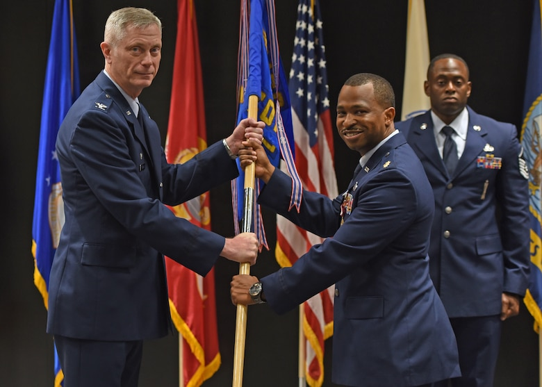 U.S. Air Force Col. Tony England, 17th Mission Support Group commander, takes the guidon from Maj. Michael Quinn, 17th Contracting Squadron outgoing commander, during the 17th CONS change of command ceremony at the Event Center, June 21, 2021. Quinn was in command of the 17th CONS for three years. (U.S. Air Force photo by Senior Airman Abbey Rieves)