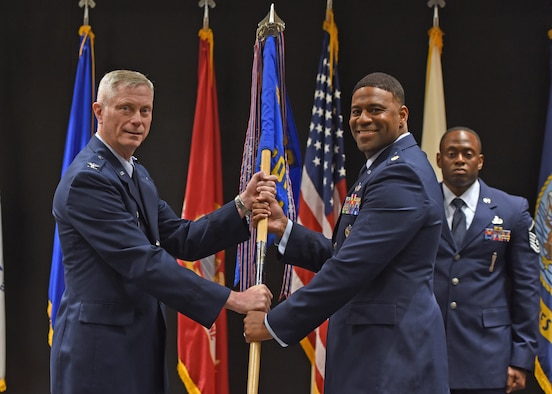 U.S. Air Force Col. Tony England, 17th Mission Support Group commander, passes the guidon to Maj. Ivan Pinder-Bey, 17th Contracting Squadron incoming commander, during the 17th CONS change of command ceremony at the Event Center, June 21, 2021. Pinder-Bey was previously student at Air Command and Staff College on Maxwell Air Force Base, Alabama. (U.S. Air Force photo by Senior Airman Abbey Rieves)