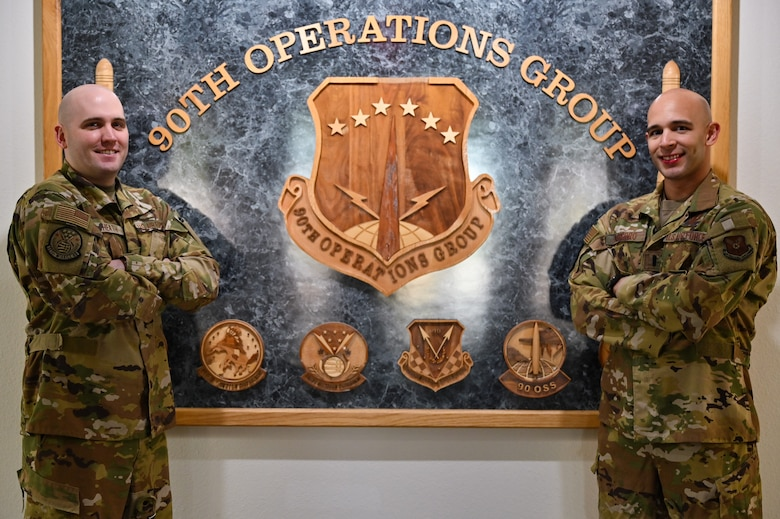Capt. Christian Heath and 1st Lt. Juan Navarro, 321st Missile Squadron combat crew, pose in front of the 90th Operations Group emblem on F.E. Warren Air Force Base, Wyoming, June 17, 2021. The Air Force Association awarded Heath and Navarro the 2020 Gen. Thomas S. Power Outstanding Missile Crew Award. (U.S. Air Force photo by Joseph Coslett)
