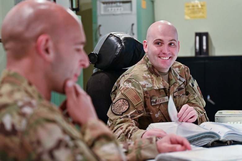 pt. Christian Heath, 321st Missile Squadron, discusses a procedural checklist with 1st Lt. Juan Navarro, 321 MS, during training in the Missile Procedures Trainer on F.E. Warren Air Force Base, Wyoming, June 17, 2021. The Air Force Association awarded Heath and Navarro the 2020 Gen. Thomas S. Power Outstanding Missile Crew Award. (U.S. Air Force photo by Joseph Coslett)