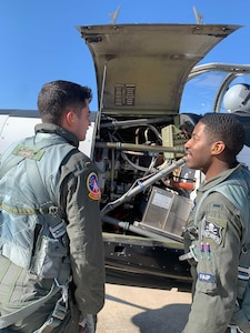 1Lt Courtland White stands outside air craft with 2Lt Skylar Reese, pointing at air frame