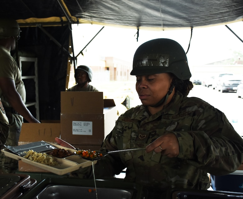 An Airman serves food on a paper tray in a field kitchen.