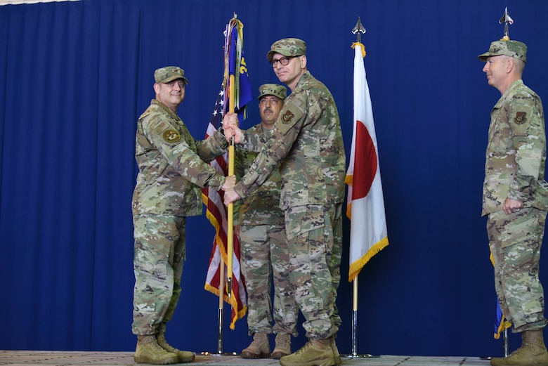 Two uniformed military members hold a guidon while looking at a picture.