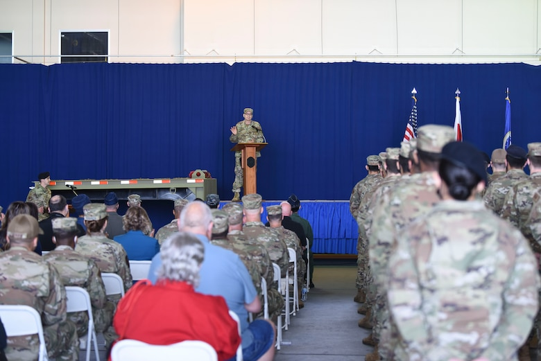 A military member in uniform stands on a stage behind a podium speaking to a crowd of civilians and military members seated to the left side and a flight of uniformed military members standing at parade rest at the right side.