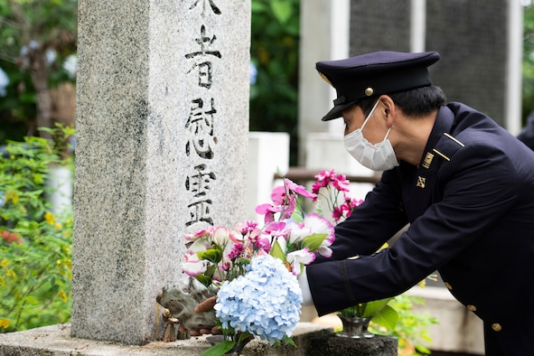 A Japanese Self-Defense Force member pours bourbon on the fallen aircrew memorial during a memorial ceremony in Shizuoka City, Japan, June 19, 2021. Individuals poured bourbon on the memorial to symbolize offering a drink for the fallen service members. (U.S. Air Force photo by Staff Sgt. Joshua Edwards)