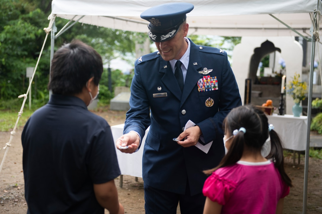 Col. Andrew Campbell, 374th Airlift Wing commander, center, gives a commander's coin to Ganchi and Motoki Sugano, the grandchildren of the event coordinator, during a memorial ceremony in Shizuoka City, Japan, June 19, 2021. Campbell gifted Sugano's grandchildren the coin as a symbol of friendship between Japan and the U.S. (U.S. Air Force photo by Staff Sgt. Joshua Edwards)