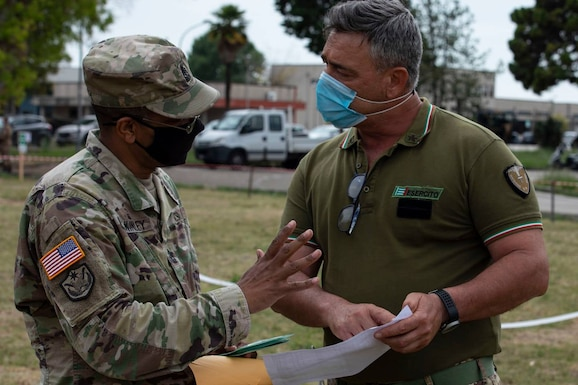U.S. Army Reserve Sgt. Maj. Forrest McKinley, senior noncommissioned officer of the 2500th Digital Liaison Detachment, 7th Mission Support Command, left, develops the base access roster for his Soldiers with Italian Army Sgt. Maj. Giovanni Di Maio during exercise DEFENDER-Europe 21, in Capua, Italy, June 10, 2021. The 2500th DLD provided liaison capability between the U.S. Army´s V Corps and the Italian Army's Divisione Acqui.