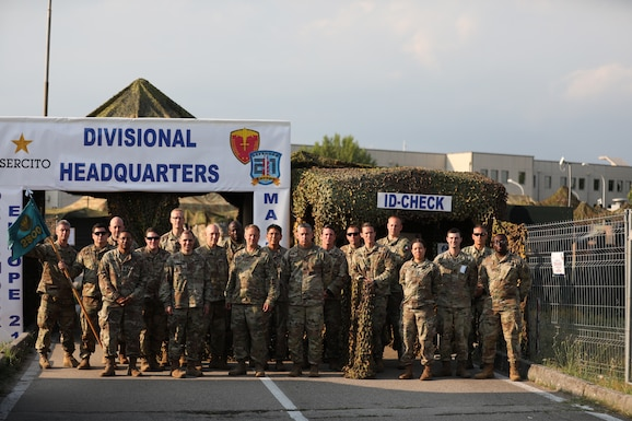 Soldiers of the 2500th Digital Liaison Detachment, 7th Mission Support Command, and the 44th Expeditionary Signal Battalion, 2nd Signal Brigade, along with evaluators from U.S. Army Southern European Task Force-Africa, pose together in front of the divisional operations center of the Italian Army´s Divisione Acqui at the conclusion of a command post exercise for DEFENDER-Europe 21 in Capua, Italy, June 14, 2021. The 2500th DLD provided liaison capability between the U.S. Army´s V Corps and the Italian Army's Divisione Acqui.
