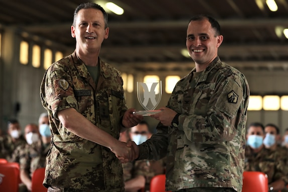 U.S. Army Reserve Col. Greg Gimenez, commander of the 2500th Digital Liaison Detachment, 7th Mission Support Command, right, presents Maj. Gen. Nicola Terzano, commander of the Italian Army´s Divsione Acqui, a unit friendship award during exercise DEFENDER-Europe 21 in Capua, Italy, June 14, 2021. The 2500th embedded with the Divisione Acqui to help with liaison support of the U.S. Army´s V Corps and Joint Force Land Component Command during the exercise.