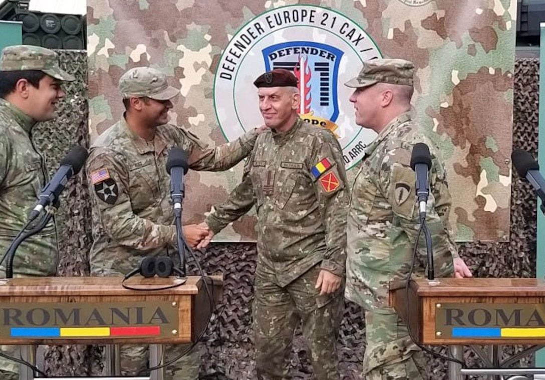 U.S. Army Reserve Maj. Allen Rust, an air and missile defense chief with the 209th Digital Liaison Detachment, 7th Mission Support Command, left, shakes hands with Romanian Army Col. Adrian Petrica of the Multi-National Command Southeast, at the close of a DEFENDER-Europe 21 command post exercise in Bucharest, Romania, June 14, 2021. The 209th DLD provided liaison capability between the U.S. Army´s V Corps, Joint Force Land Component Command and the Romanian MNC-SE.