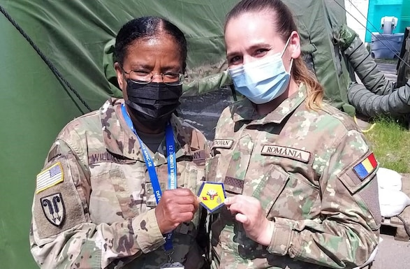 U.S. Army Reserve Brig. Gen. Wanda N. Williams, commander of the 7th Mission Support Command, shares her coin and a photo with a Romanian Army Multi-National Command Southeast Soldier during a visit to MNC-SE headquarters for exercise DEFENDER-Europe 21 in Bucharest, Romania, June 13, 2021. Soldiers of the 209th Digital Liaison Detachment, 7th MSC, provided liaison capability between the U.S. Army´s V Corps, Joint Force Land Component Command and the Romanian MNC-SE.