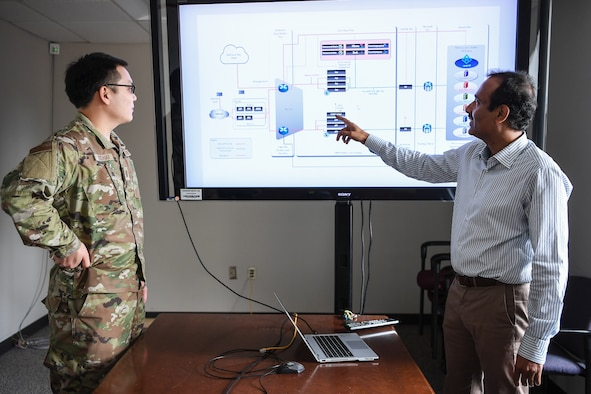 Raju Ranjan, an engineer from the AFNet Sustainment and Operations Branch discusses plans for a modern software-based perimeter with Capt. Christopher Kodama, a Branch engineer, at Hanscom Air Force Base, Mass., June 3.
