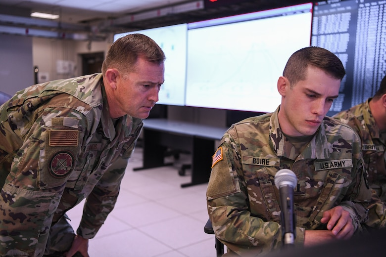 Lt. Col. Darren Edmonds, director of the Lantern, also known as the Hanscom Collaboration and Innovation Center, looks on as 1st Lt. Nicholas Boire, from the Massachusetts National Guard's 126th Cyber Protection Battalion, reviews data during a proof of concept event at Hanscom Air Force Base, Mass., May 20.