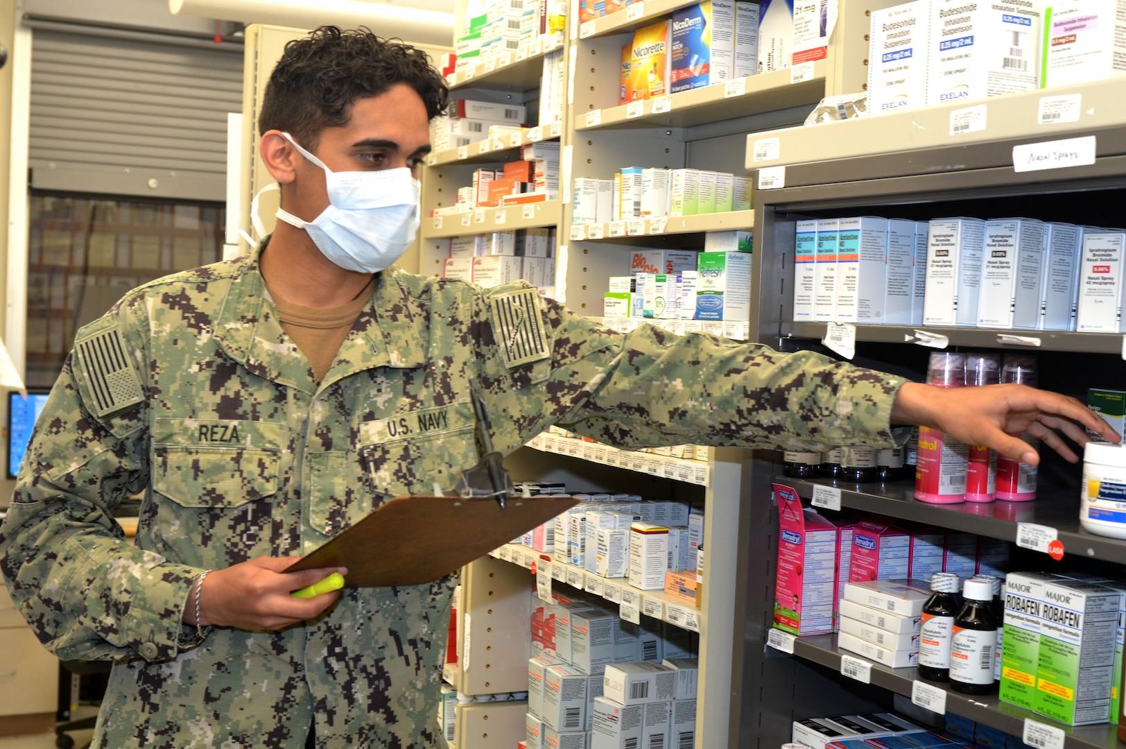 Service member reaches for medicine in pharmacy
