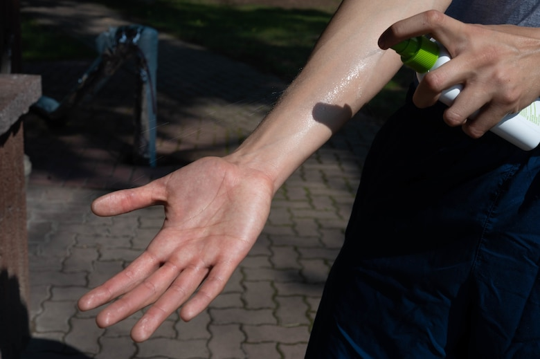 Airman applies insect repellent to arm.
