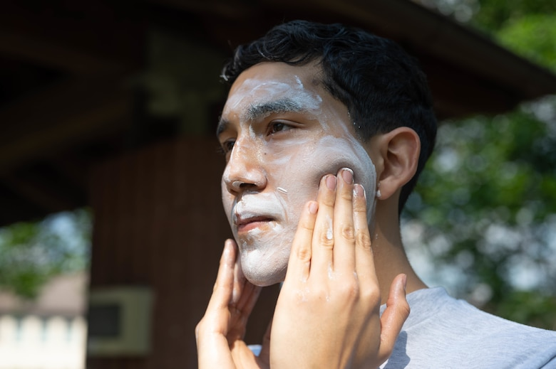 Young Airman applies too much sunscreen to face.